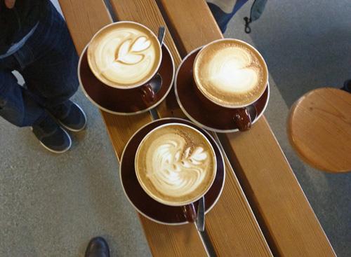Three cafe lattes waiting to be enjoyed.