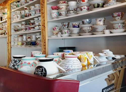Coffee shop with dozens of different coffee cups.
