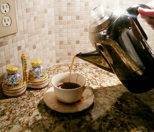 Pouring from a coffee percolator.