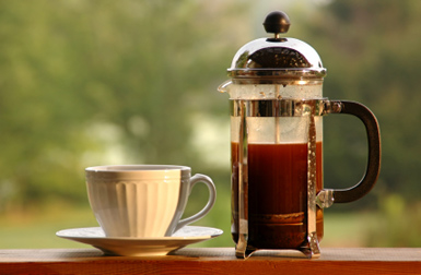french press coffee maker and coffee cup