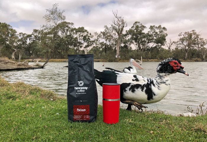 The Cafflano coffee maker by the water, with a bag of coffee... and duck.