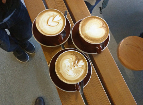 Three cafe lattes waiting to be enjoyed.