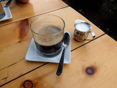 An Americano with hot milk on the side.