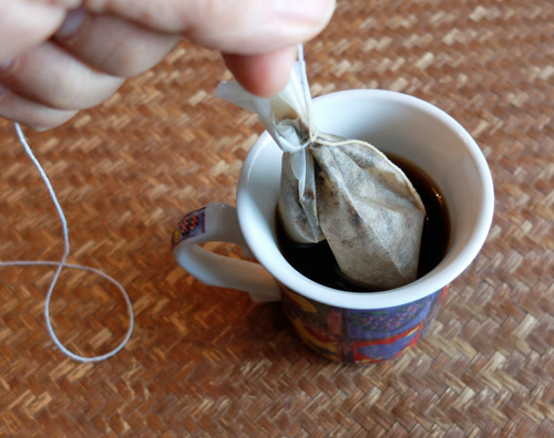 Making a coffee bag with a paper filter and string.