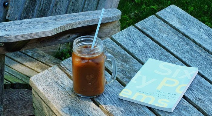 Poetry book with iced coffee in glass
