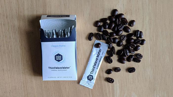 Paquet d'eau de la troisième vague avec des grains de café